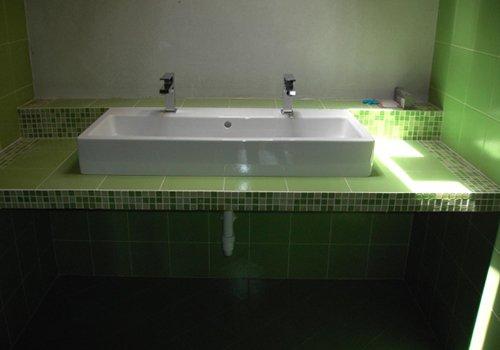 una mensola con le piastrelle verdi e un lavabo con due rubinetti