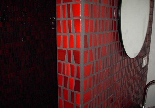 un muro di color grigio con le piastrelle di color rosso
