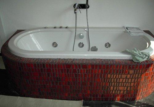 una vasca con le piastrelle intorno di color rosso e arancione