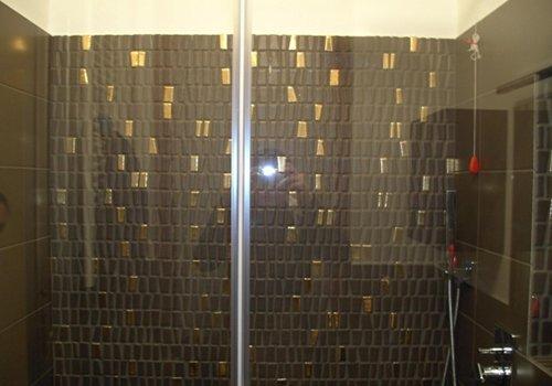 un box doccia con i muri in piastrelle di color nero e dorato