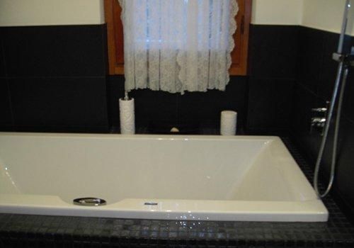 una vasca con le piastrelle di color grigio intorno