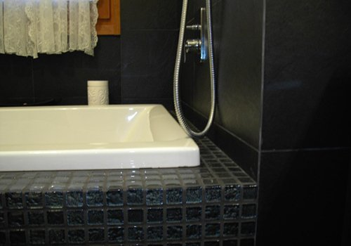 una vasca con le piastrelle di color grigio scuro  intorno
