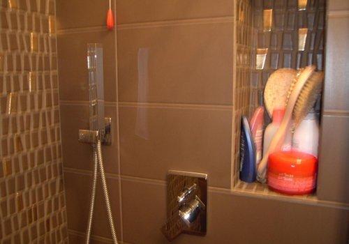 muri di una doccia con le piastrelle di color marrone e dorato