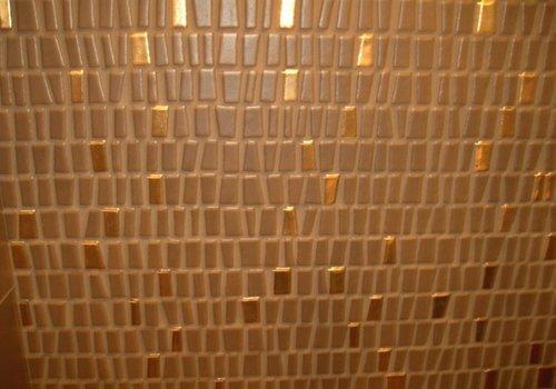 un muro con le piastrelle di color marrone e dorato