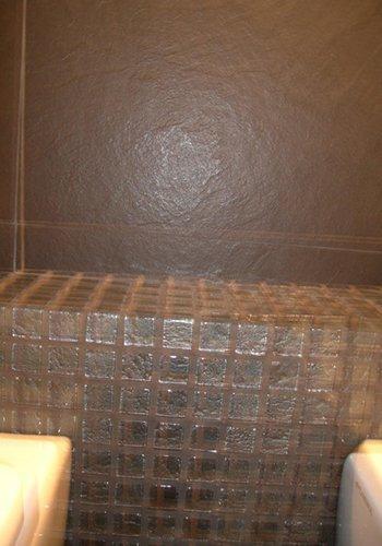 muro di un bagno con le piastrelle grigie scure