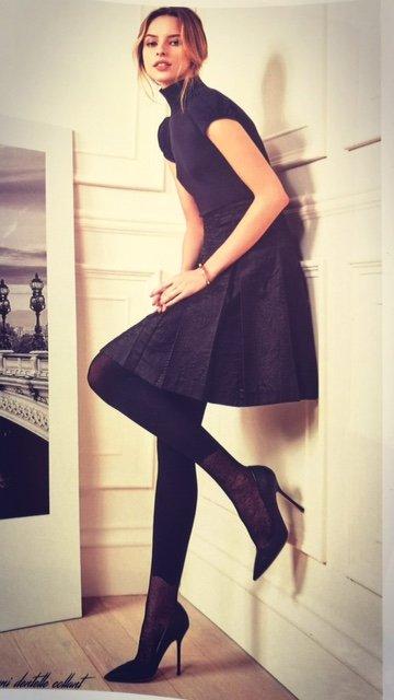 modella appoggiata al muro vestita di nero