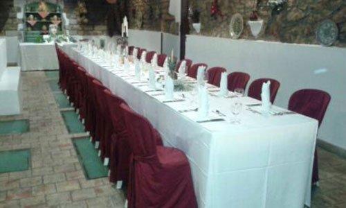 Tavoli rotondi con tovaglie bianche e bouquet di fiori all'esterno