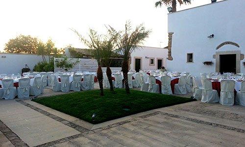 Tavoli rotondi con tovaglie, copri sedie di color bianco e un'aiuola al centro con delle palme