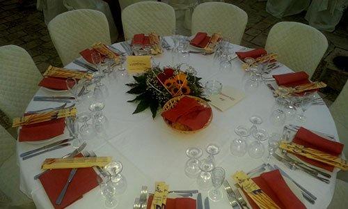 Una tavola rotonda apparecchiata con piatti, bicchieri tovaglioli arancioni e al centro un bouquet di girasole
