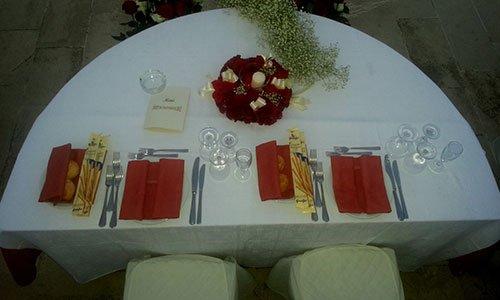 Una tavola apparecchiata per gli sposi con bicchieri, tovaglioli arancioni e un bouquet di fiori rossi con una candela bianca al centro