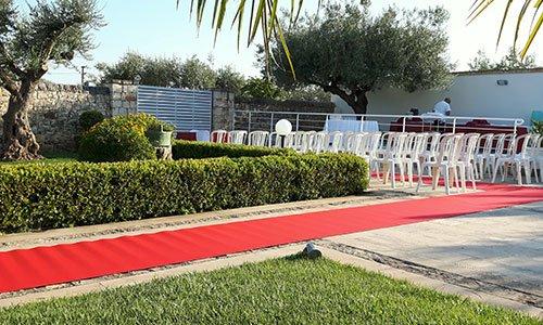 un tappeto rosso sulla camminata e tante sedie di plastica messe all'esterno