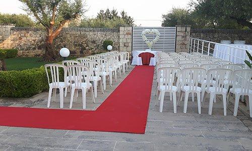 un tappeto rosso in un giardino con sulla sinistra un albero e dei fiori gialli,in centro delle sedie di plastica disposte a file, davanti un tavolo con una tovaglia bianca e dietro ad esso un cancello con un cuore formato da piccoli palloncini