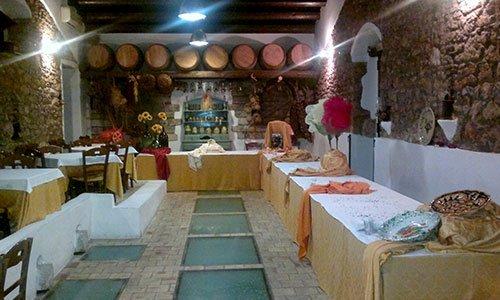Una stanza con un buffet angolare con vasi di fiori e piatti decorativi,sul lato destro dei tavoli con tovaglie bianche e in fondo una mensola con barili