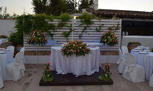 All'esterno del ristorante tavoli rotondi con tovaglie bianche, un piccolo alatrino in legno con un tavolo e un bouquet di fiori