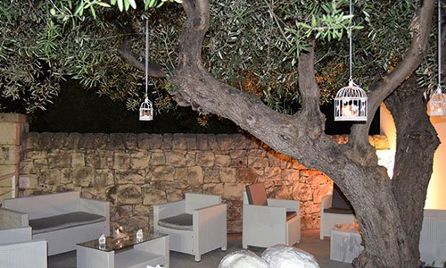 Divani e poltrone da esterno sotto un albero con lumini appesi durante la sera