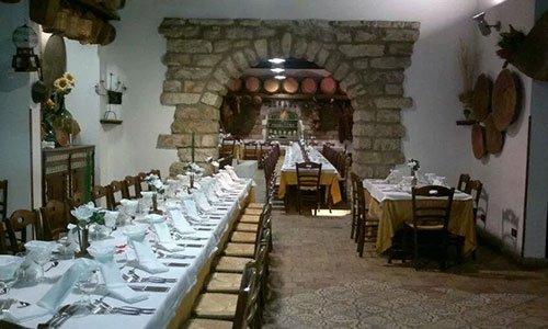 sala all'interno del ristorante con sulla sinistra una lunga tavolata apparecchiata sulla destra un tavolo da sei persone e al centro un' arcata che porta alla sala successiva con altre tavolate