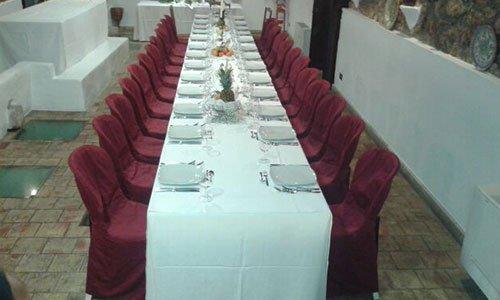 una lunga tavolata apparecchiata con una tovaglia bianca e delle sedie rivestite con un tessuto bordeaux