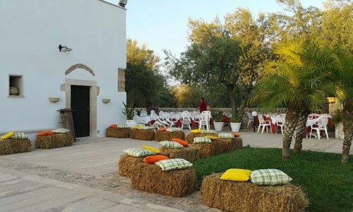 un giardino con palme tavoli e sedie di plastica e balle di fieno a forma quadrata con sopra dei cuscini colorati
