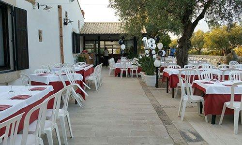 all'esterno del ristorante tavoli e sedie in plastica, un ulivo , delle piante e dei palloncini bianchi e neri con al centro una scritta che raffigura il numero