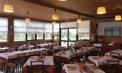 sala all'interno del ristorante con tavoli e sedie in legno e sul soffitto delle lampade a sospensione