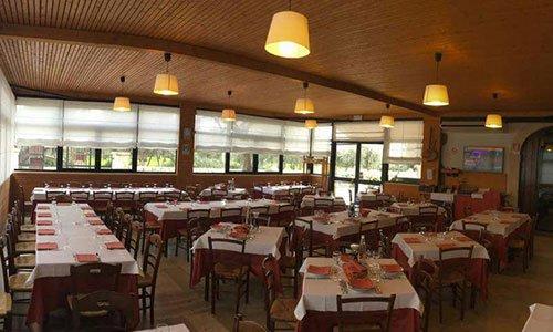 sala del ristorante con tavoli e sedie di legno e lampade che pendono dal soffitto