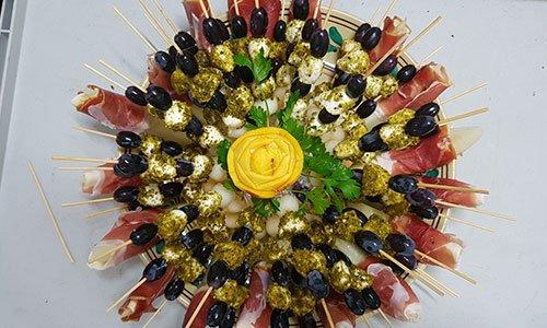 Un piatto con spiedini di formaggio, salumi, olive nere e al centro una verdura a forma di un fiore