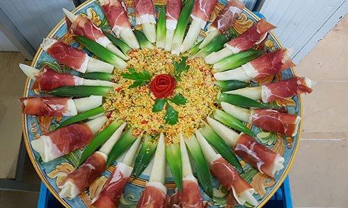 Un piatto con fette di melone e salumi arrotolati impiattati a  forma di un fiore