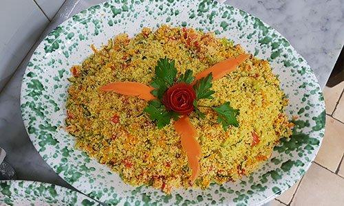 Una ciotola con cous cous con  fette di carote e foglie del coriandolo