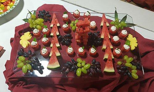 Una vassoio di vetro con uva nera, bianca e fette di anguria tagliate a forma di triangolo, rotondo e rettangolari