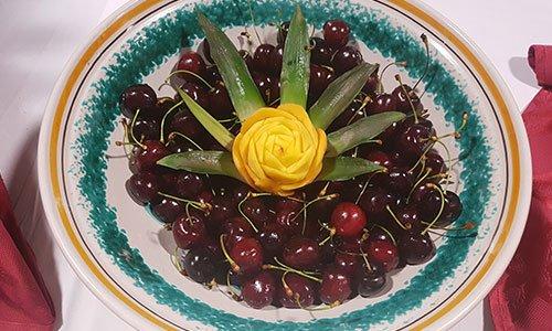 Una ciotola con ciliegie e al centro una pesca tagliata a forma di una rosa