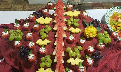 Un vassoio di vetro con uva nera, bianca, fette di  ananas e anguria tagliata a forma di triangolo e circio