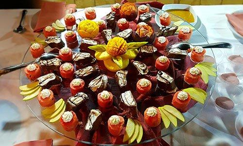 Un vassoio con con frutta tagliata a varie forme e decorazione con la panna
