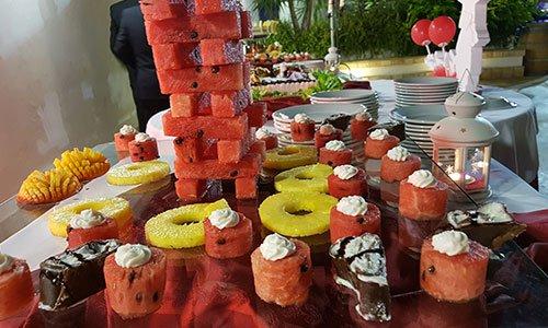 Un buffet con fette di anguria e ananas a varie forme e altri dolci esposti su un vassoio di vetro