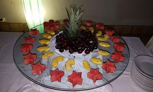 Un vassoio di vetro con ciliegi al centro e intorno fette di anguria tagliati a forma di stelle