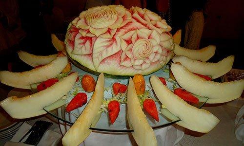 Un vassoio con  frutta varia, fette di melone e un'anguria con disegni a fiori al centro