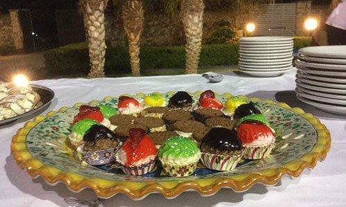 Un buffet all'esterno con un piatto di cupcake colorati e al centro dei biscotti al cioccolato