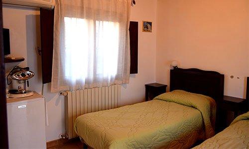 Una stanza con due letti singoli, aria condizionata al muro e una mensola con un Tv