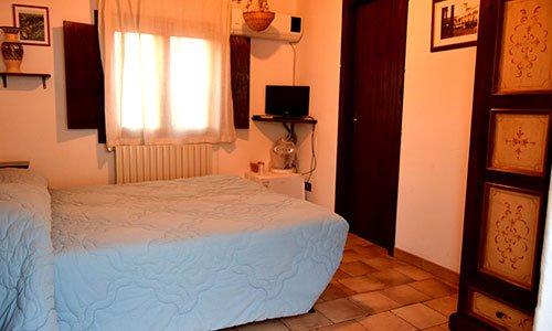 Una stanza con un letto matrimoniale, un tv sulla mensola, una finestra aperta e aria condizionata al muro