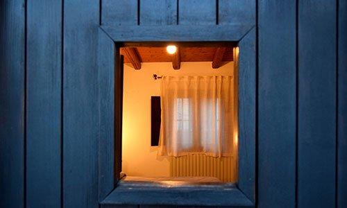 Vista da lontano di una finestra e dentro si vedono dei caloriferi e una tenda