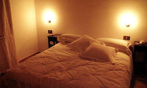 Un letto matrimoniale con piumone,cuscini bianchi e due luci accese sopra comodini