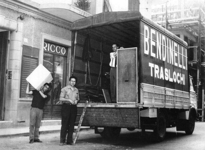 una foto in bianco e nero di alcuni traslocatori e un camion