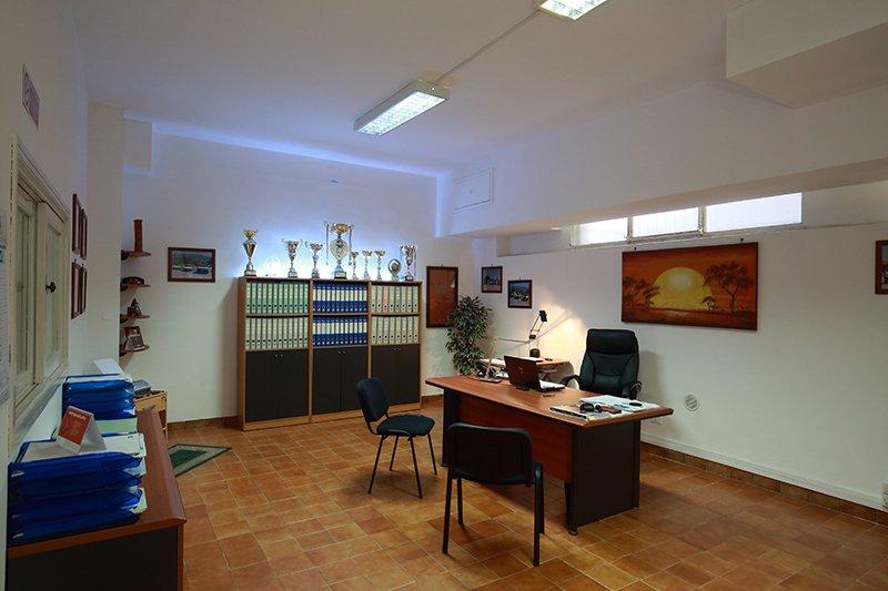 ufficio visto da un'altra angolazione con vista sulla sinistra di un mobile con sopra dei fascicoli di color blu e di fronte un mobile con una segne di raccoglitori disposti all'interno