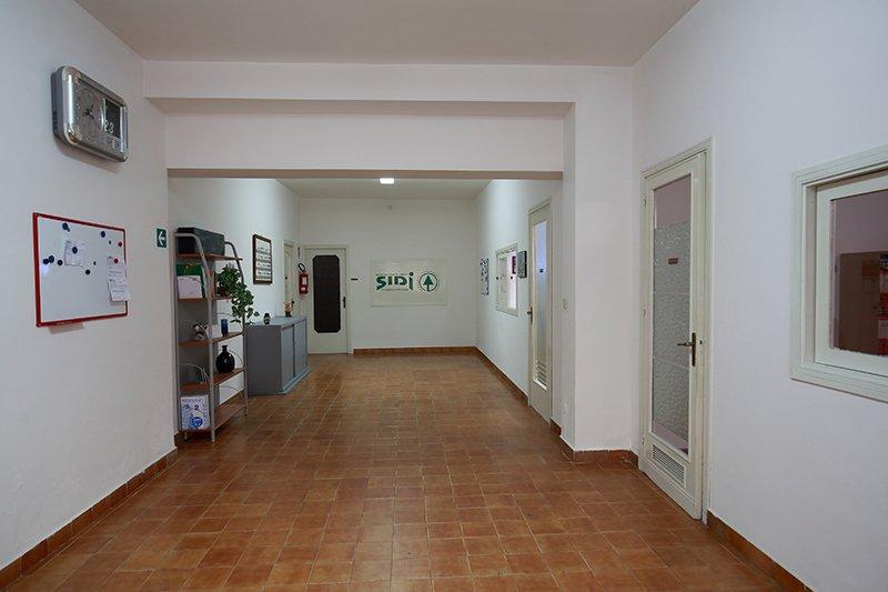 un corridoio con sulla sinistra una lavagna magnetica, un orologio grigio a muro, uno scaffale con degli oggetti e una pianta e in fondo un armadio in metallo