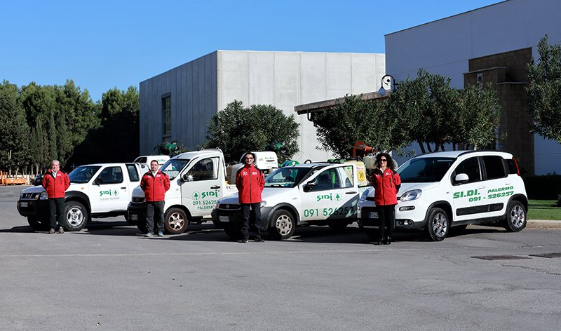 4 furgoni e auto da lavoro color bianco parcheggiati nella zona industriale e davanti a ogni veicolo delle persone con una divisa color rosso che posano per una foto