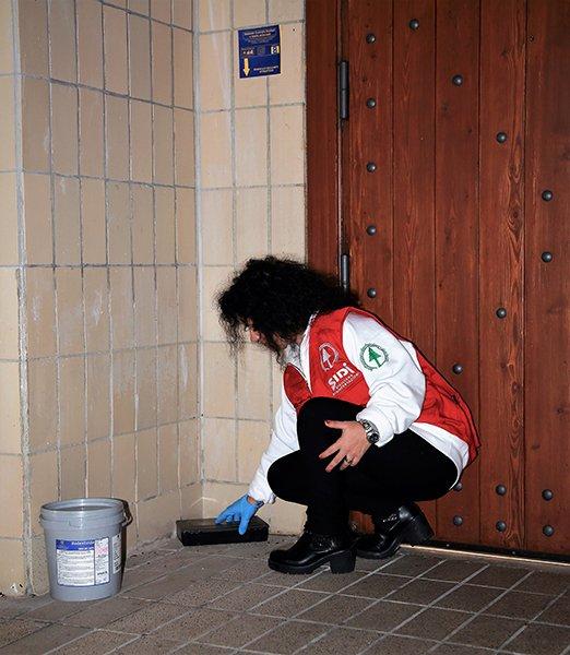 donna inginocchiata per terra mentre posiziona una trappola da derattizzazione, accanto a lei una porta in legno e sulla destra un secchio grigio