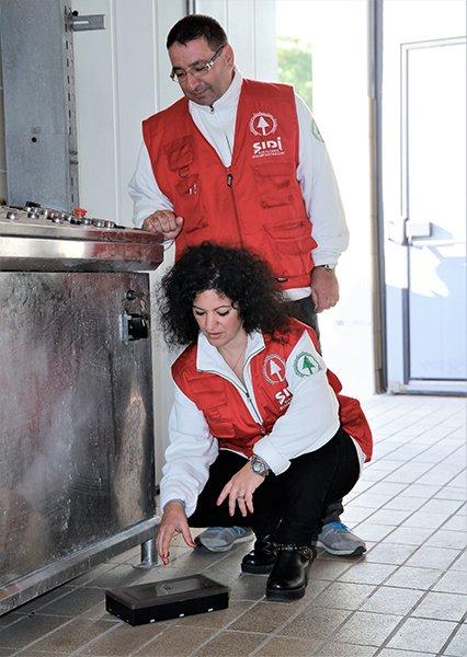 una donna inginocchiata posiziona una trappola da derattizzazione e dietro di lei, in piedi, un uomo monitora il suo operato