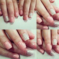 Delle mani di una donna con uno smalto di color rosa chiaro e alcune unghie di color bianco