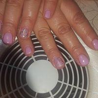 le mani di una donna mentre asciuga lo smalto lilla  davanti a un fornetto