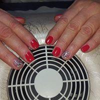le mani di una donna mentre asciuga lo smalto rosso davanti a un fornetto