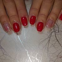 Mani di una donna con smalto di color rosso e alcune unghie con smalto rosa